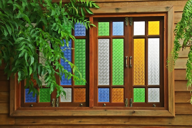 Stained glass window, thai style wooden window with green leaves.