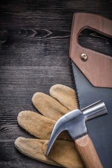 Stainless hack-saw claw hammer protective leather gloves on wood board