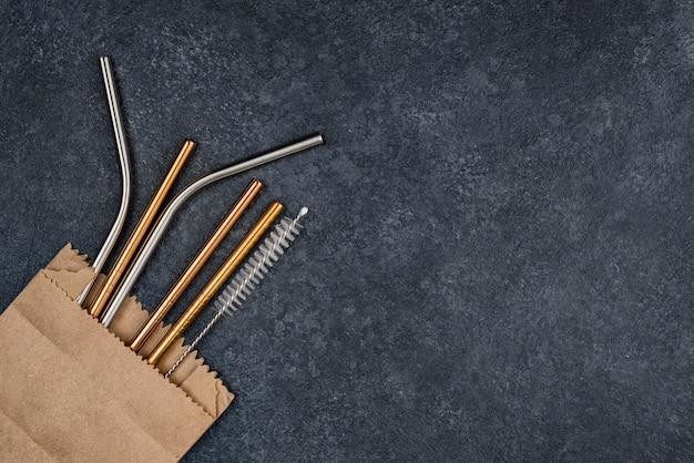 Металлические соломинки из нержавеющей стали в копировальном пространстве бумажного пакета
