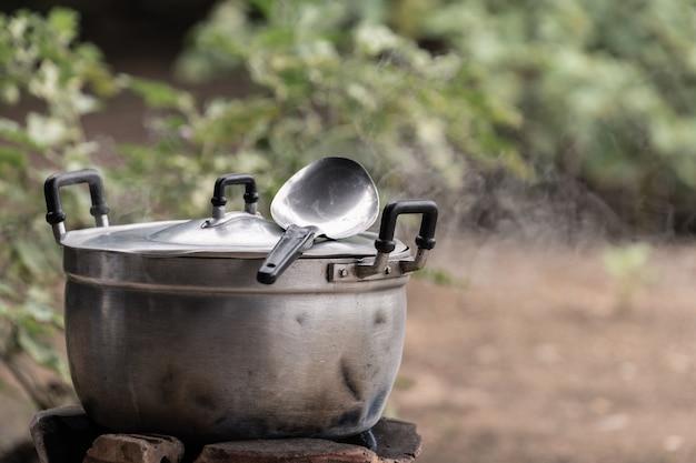 煙を伴う朝の光での取鍋でのステンレスポットの調理