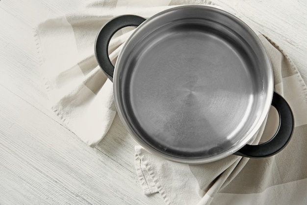 Stainless saucepan and napkin on white wooden table