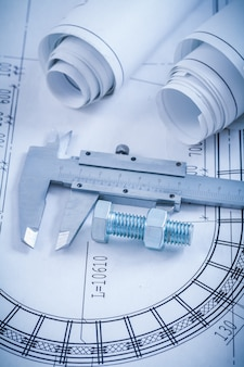 Stainless screw bolt with nut slide caliper rolls of construction plans on blueprint architecture and building concept