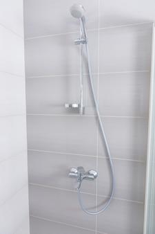 건축 배경에 유리문이 있는 회색 타일 샤워실 내부의 스테인리스 스틸 및 크롬 샤워 피팅