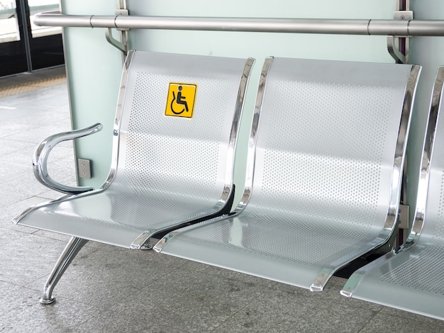 Stainless steel chairs in the train station with disabled signage to facilitate the use