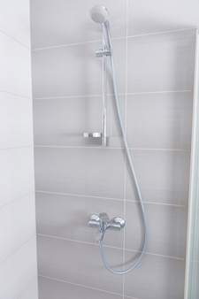 Stainless steel and chrome shower fittings inside a grey tiled shower cubicle with glass door in an architectural background