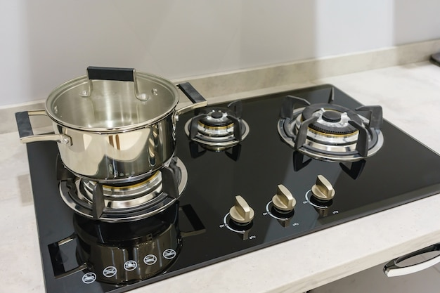 Stainless steel cooking pot on gas stove in contemporary modern home kitchen
