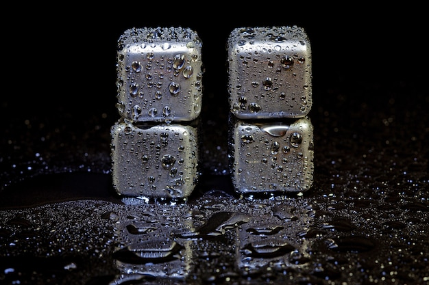Stainless steel cubes simulating ice for cooling drinks on a black surface with a reflection.
