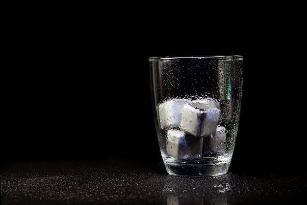 Stainless steel cubes simulating ice in whisky glass on a black table.