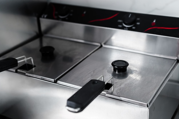 Stainless steel deep fryer machine in professional kitchen close up