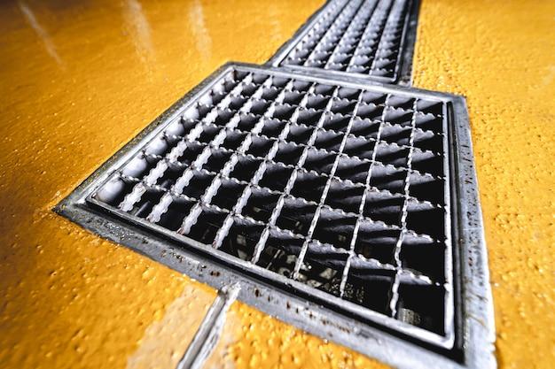 Слив в полу из нержавеющей стали на современном пивоваренном заводе