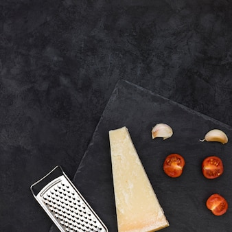 Stainless steel grater with cheese block; garlic cloves and halved tomatoes on slate rock over the black background