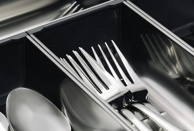 工具、スプーン、フォークのシンプルなセットを備えたステンレス鋼の台所用品カトラリー引き出しオーガナイザートレイ。閉じる。