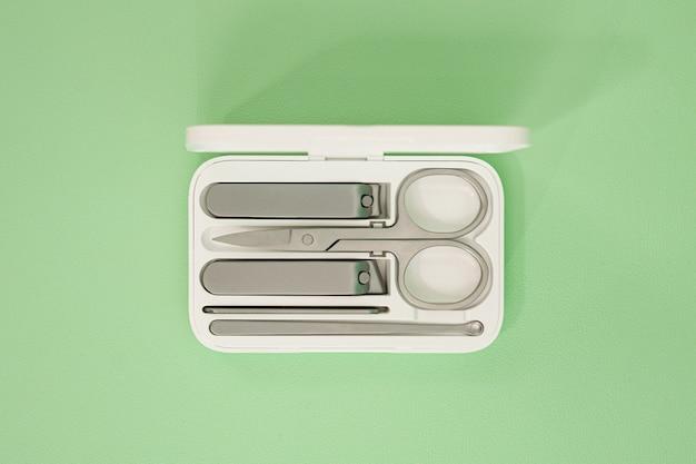 薄緑色の背景に白いスタイリッシュな収納ボックスにセットされたステンレス鋼の爪切り。