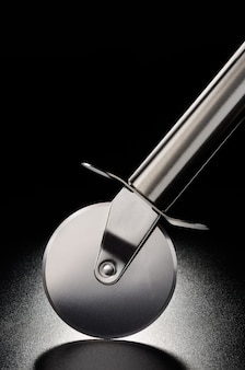 Stainless steel pizza cutter on black matt background