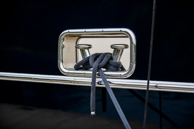 Столбик из полированной нержавеющей стали с швартовным тросом на темно-синем корпусе супер роскошной яхты.