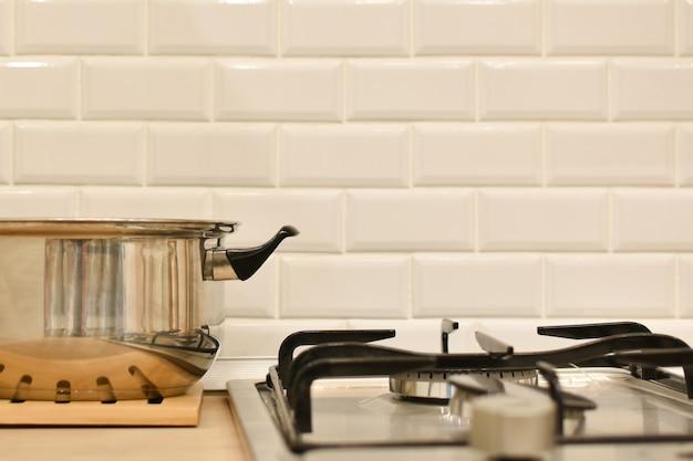 ステンレス鋼の鍋は白いレンガの台所の壁に対してガスバーナーの隣に立っています。ガスストーブと調理器具を備えたキッチンインテリア。台所用品。食品を調理するための作業スペース。台所用品。テキスト用のスペース
