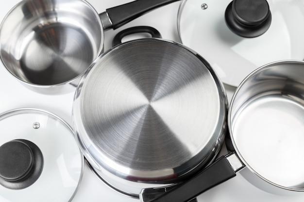 Кастрюли и сковородки из нержавеющей стали, изолированные на белом