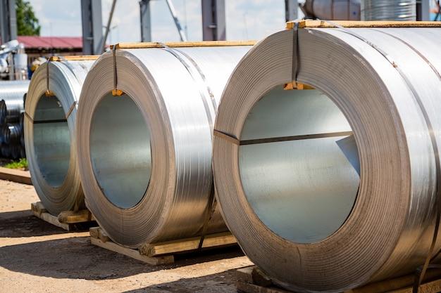 Рулоны из нержавеющей стали. рулоны стального листа на складе. рулон оцинкованного стального листа для производства металлических труб на заводе.