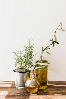 ステンレス鋼ローズマリーポット、木製テーブルに油のボトル