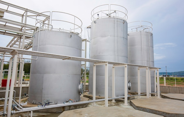 Stainless steel silos in the chemical industry, bulk plastics silo against a blue sky