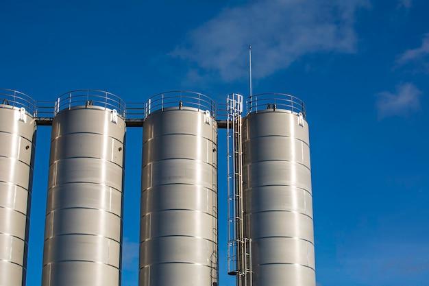 化学産業のステンレス鋼サイロ、青い空を背景にしたバルクプラスチックサイロ