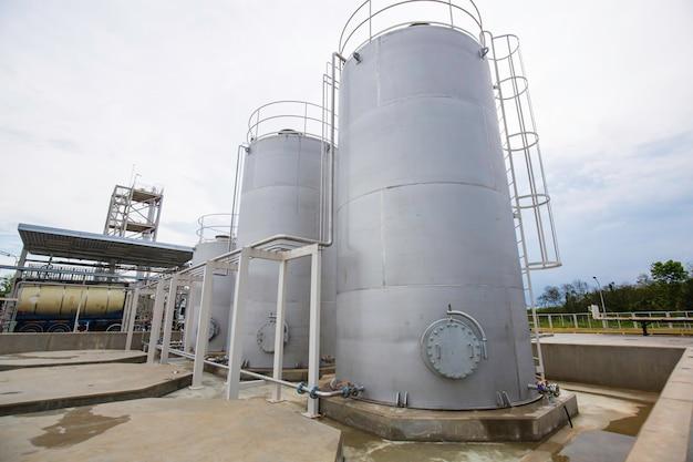 Силосы из нержавеющей стали в химической промышленности, силосы для сыпучих материалов на фоне голубого неба.