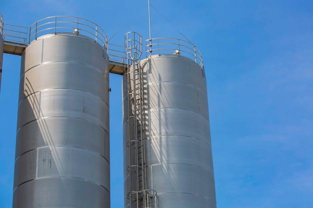 화학 산업의 스테인리스 스틸 사일로, 푸른 하늘을 배경으로 한 벌크 플라스틱 사일로