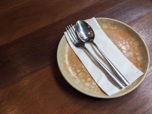 木製のテーブルの上のビンテージスタイルの円形セラミックプレート上の白いきれいなナプキンのステンレス鋼のスプーンとフォーク