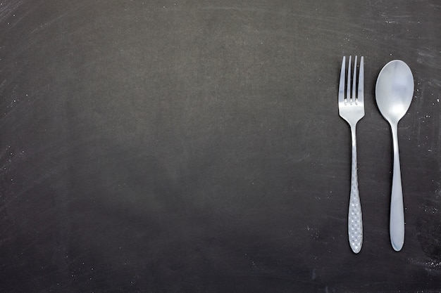 Stainless steel spoon and fork on black wood or chalkboard background with copyspace
