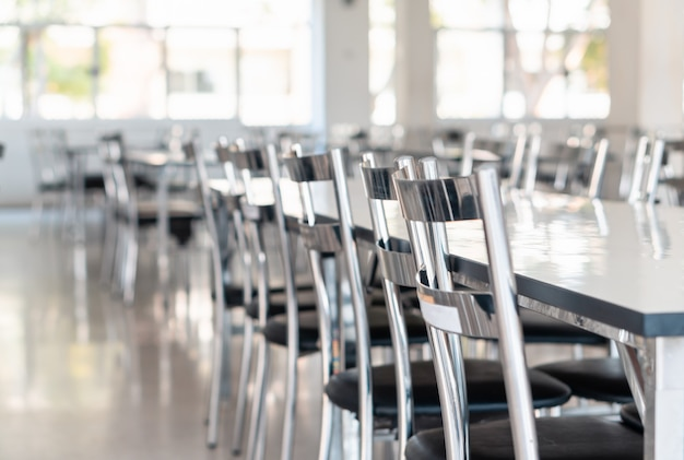 Stainless steel tables and chairs in high school student canteen,