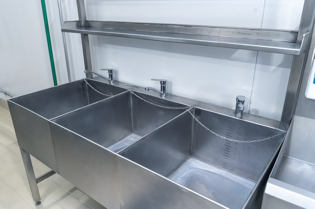 Stainless steel washbasins for disinfection.