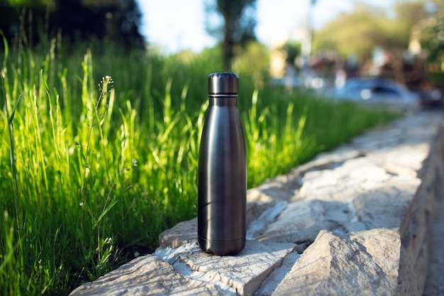 Stainless thermo water bottle of black on background of green grass. reusable bottles zero waste eco concept plastic free.
