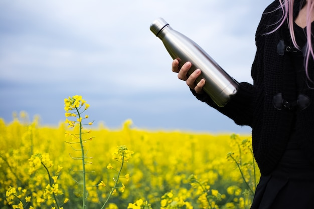 Stainless thermos bottle in hand, on surface of rapeseed field.