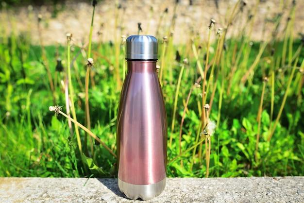 緑の草の上に隔離されたステンレス製の魔法瓶ウォーターボトル水コピースペースのコンセプトのための屋外のスチール製魔法瓶光沢のあるボトルプラスチックを使用しないゼロウェイスト