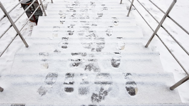 계단 난간과 눈. 미끄러운 계단, 발자국으로 덮인 얼음, 외부 수평 샷.