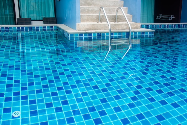 Stair of swimming pool with blue water