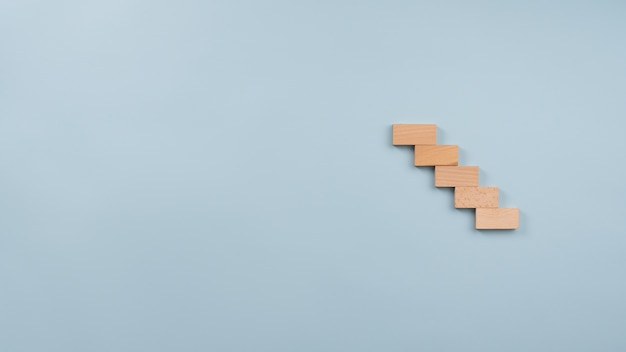 Staircase made of five wooden pegs in a conceptual image.
