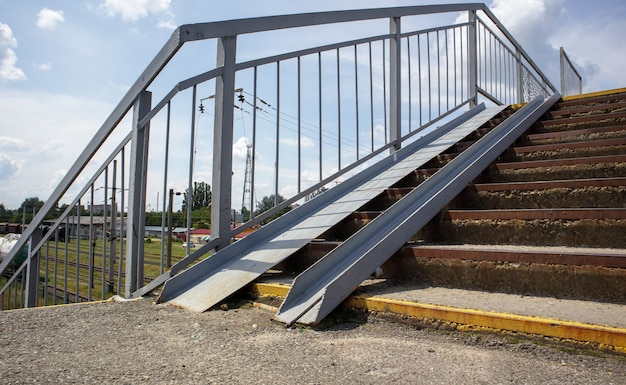 The staircase of the pedestrian crossing with traces of destruction. two wheelchair rails. metal railings for bicycles, wheelchairs and strollers with children. special equipment on the stairs.