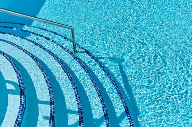 Staircase to the swimming pool with blue water on a tropical resort