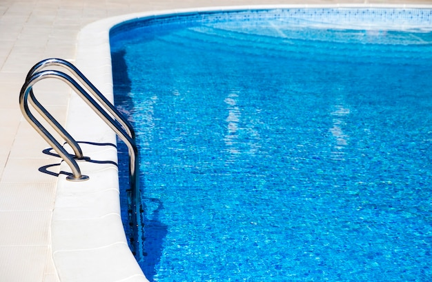 青い水の美しいプールへの階段