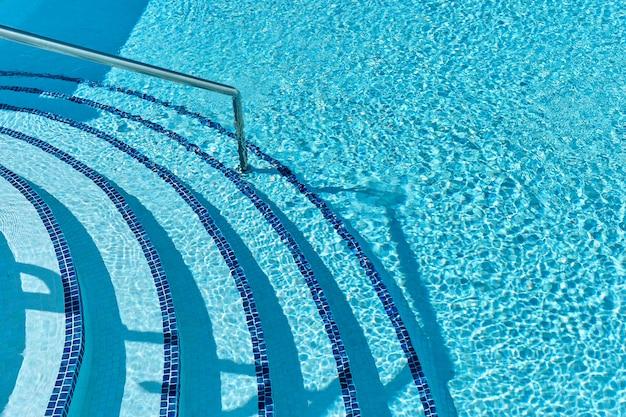 Лестница к бассейну с голубой водой на тропическом курорте
