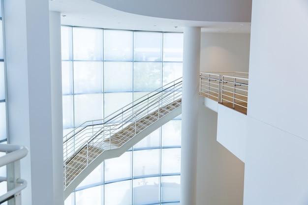 Лестница с металлическими перилами у стеклянной стены
