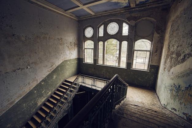 더러운 벽이있는 오래된 버려진 건물의 계단