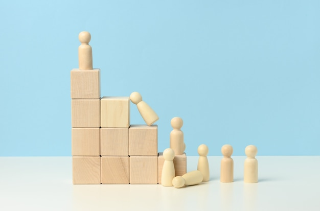 Stairs from wooden cubes and a crowd of fallen wooden figures of men on a blue background. the concept of competition in business, career. burnout in the workplace, goal achieves strong