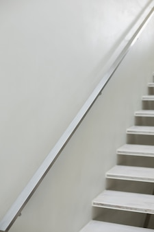 Stairs and hand rails along white wall