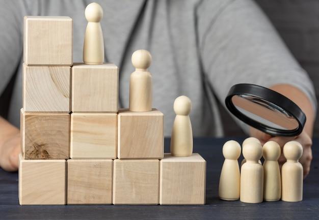 나무 큐브와 남성 인형으로 만든 계단, 돋보기가 달린 손이 그룹을 검사합니다. 모집 개념, 재능있는 직원 및 리더 검색, 경력 향상
