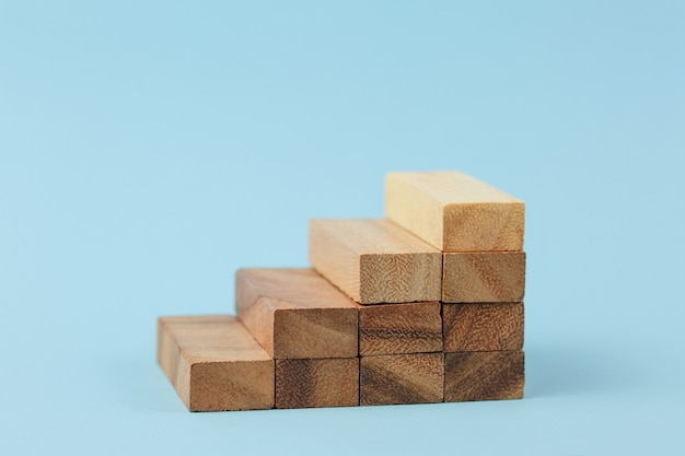 Stairs of natural color wooden blocks on blue wall. concept of growth and success plan.