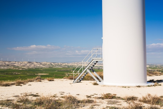 Stairs on wind mill during bright summer day green meadow with wind turbines generating electricity