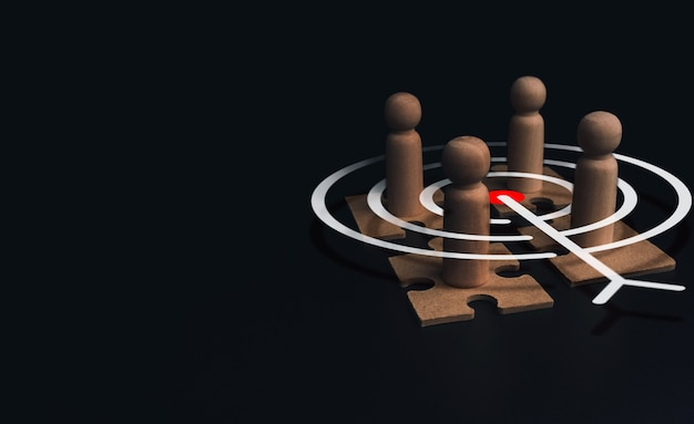 Stakeholder, business connection, teamwork, and team building concept. close-up wooden figure, as businessman on jigsaw puzzles with target icon symbol on dark background with copy space.