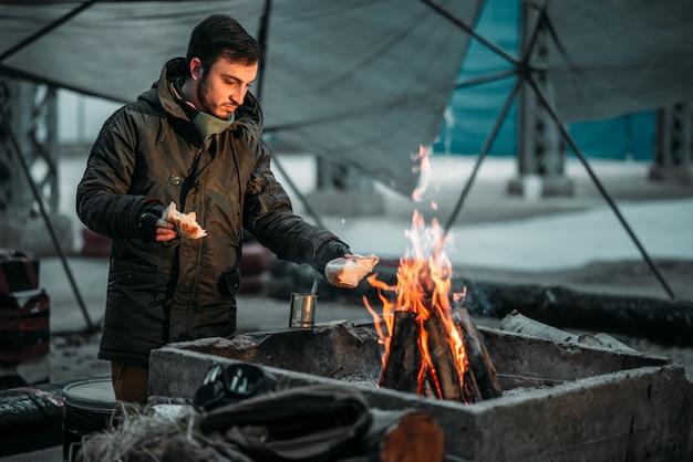 Сталкер готовит еду в огне